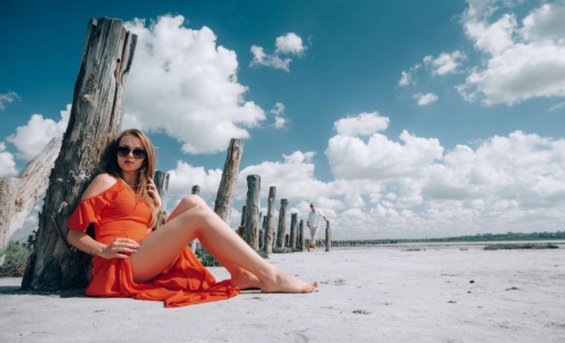 Frau im roten Kleid beim SandstrandSEO am Meer
