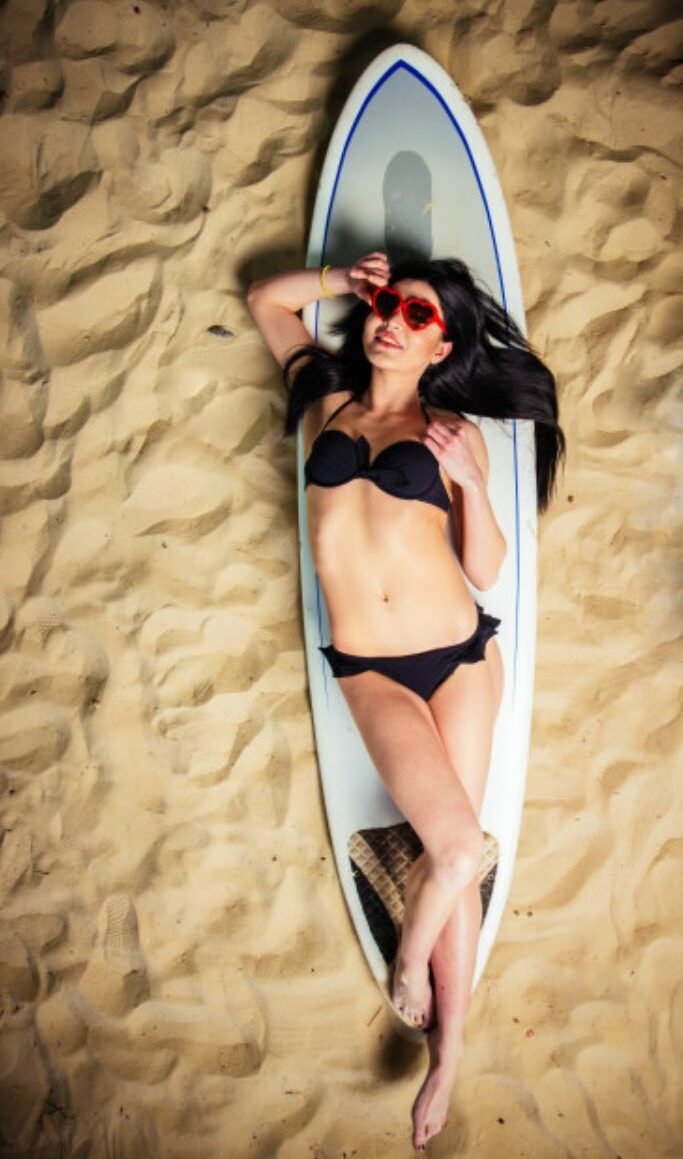 Frau mit schwarzem Bikini auf Surfbrett am SandstrandSEO